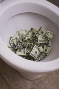 dirty toilet with money close up, lot of cash useless